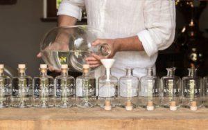 Aejist gin, man in white shirt fills 10 bottles with gin through white funnel