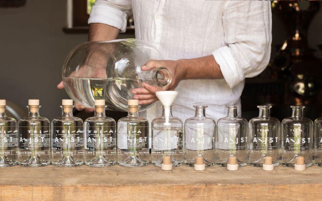 Aejist gin, man in white shirt fills 7 bottles with gin through white funnel